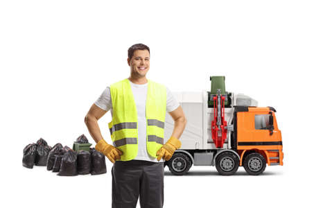 Waste collector in a uniform and gloves standing in front of a garbage truck isolated on white background Imagens