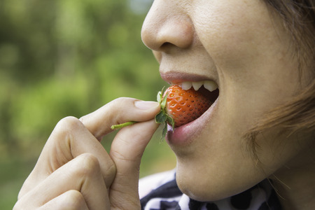 Macro view of a pretty young female eating fresh strawberry photo
