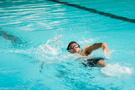 backstroke: young man swimming in backstroke in a pool.