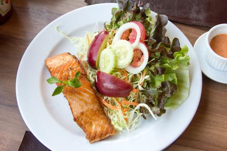 king salmon: Salmon fish steak with  Vegetable salad on plate. Stock Photo