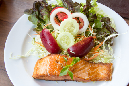 king salmon: Salmon fish steak with  Vegetable salad on plate. Stock Photo