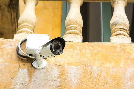 business security: CCTV security camera it under old balcony at plaza. Stock Photo