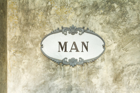 exposed concrete: Men sign in vintage frame style on exposed concrete wall.