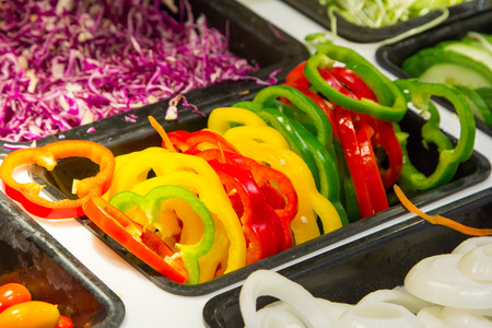 red bell pepper: Green, yellow, red bell pepper slices on salad bar.