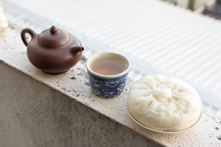 Chinese teapot and Chinese tea and dumplings streamed on the balcony., Chinese cuisine. Stock Photo