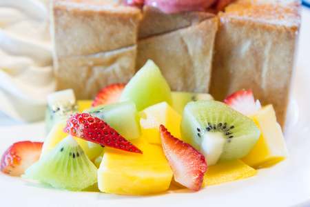 luscious: Honey toast with fruit and ice cream on a white plate.