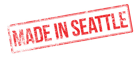 accomplish: Made in Seattle red rubber stamp on white. Print, impress, overprint.