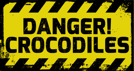 warned: Danger crocodiles sign yellow with stripes, road sign variation. Bright vivid sign with warning message.
