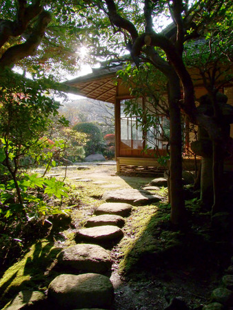 A stone path leads to a Japanese temple as the sun wanes.