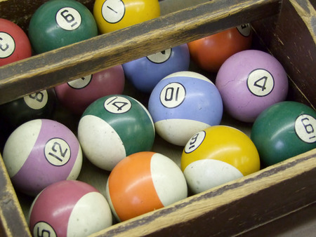 pool halls: Old, worn billiard balls sit organized in a tray Stock Photo