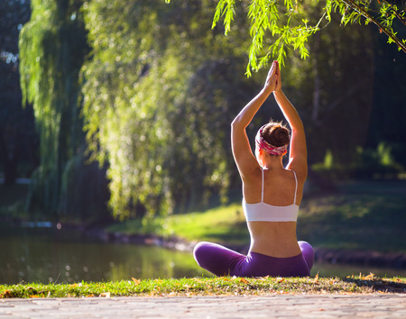 Young woman doing yoga in morning park