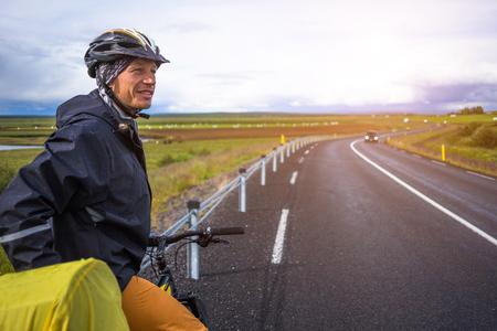 bicicleta: hombre feliz durante viaje de bicicletas en Islandia Foto de archivo