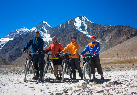 Young happy friends cyclists standing on road in Himalayas mountains , North India