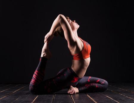 femme blonde: Belle jeune et en forme modèle sport de fitness yoga en studio sombre Banque d'images