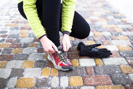 frio: Deporte joven mujer modelo de atar los zapatos para correr durante el entrenamiento de invierno fuera en el fr�o de la nieve en el parque
