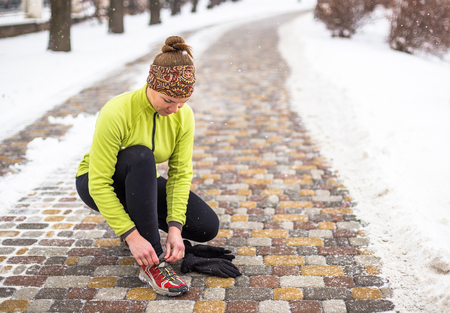 winter park: Young sport woman model tying running shoes during winter training outside in cold snow weather in park