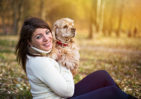 american cocker spaniel: Young beautiful woman and her dog (American Cocker Spaniel) posing outside at fall time