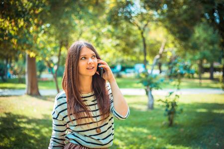 Hermosa mujer joven hablando por un teléfono en el parque de la ciudad.