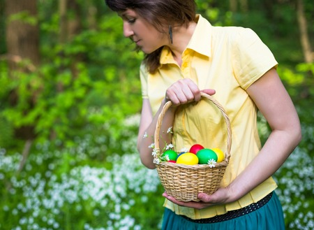cute lady: Young woman with Basket of easter eggs on meadow, Closeup picture