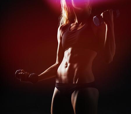 Muscular fitness woman posing on dark background
