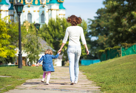 mothercare: Happy girl-kid walking with her mother in city park.