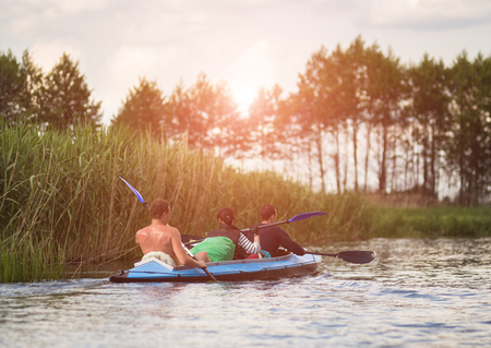 canoeing: Young people are kayaking on a river in beautiful nature.