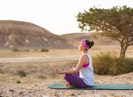 Young woman doing yoga in desert at sunrise time. Summer hot weather