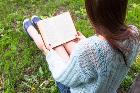 personas leyendo: Adolescente feliz chica leer un libro en el parque de la ciudad al aire libre.