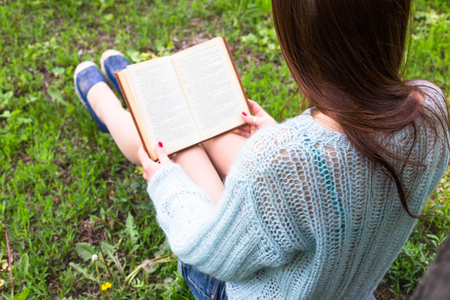 outdoor reading: Teen happy girl read a book in city park outdoor. Stock Photo