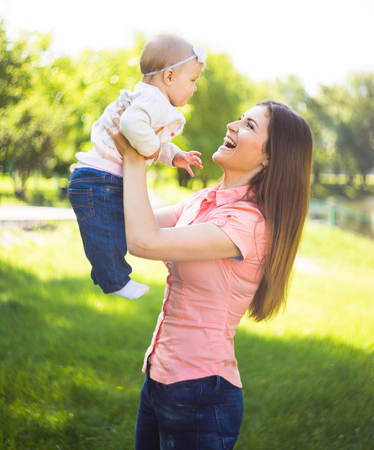 mothercare: Youmg happy woman playing with her cute baby in summer sunny park outdoor. Mothercare picture. Stock Photo