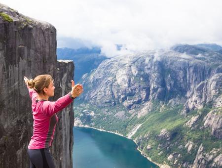 hardanger: Young woman feel freedom on Kerag. Happy woman enjoy beautiful lake and good weather in Norway Stock Photo