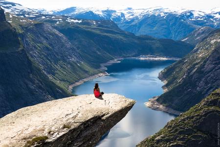 행복한 여자가 아름다운 호수와 노르웨이 좋은 날씨를 즐길 수 있습니다.