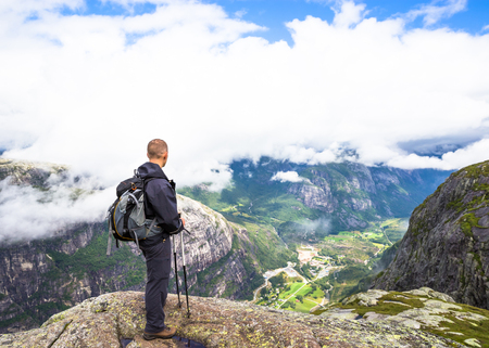 hardanger: Young woman hiking on kjerag. Happy woman enjoy beautiful lake and good weather in Norway