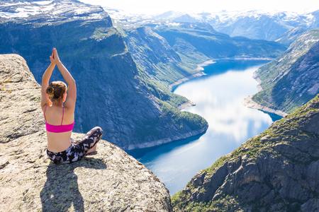 Young woman doing yoga on Trolltunga. Happy girl enjoy beautiful lake and good weather in Norway