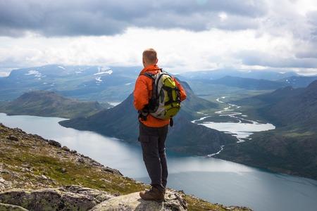 Sport mane hiking on Besseggen. Hikers enjoy beautiful lake and good weather in Norway