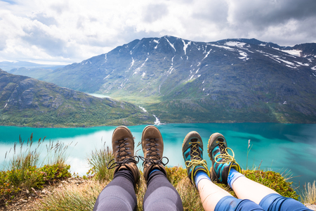Sport couple hiking on Besseggen. Hikers enjoy beautiful lake and good weather in Norway Stock Photo