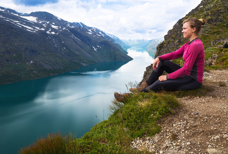 Sport woman hiking on Besseggen. Hikers enjoy beautiful lake and good weather in Norway Stock Photo