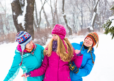 Happy friends having fun in winter cild snowing weather at park. Banco de Imagens