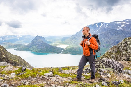 Young man hiking on Besseggen. Happy man enjoy lake and good weather in Norway Stock Photo