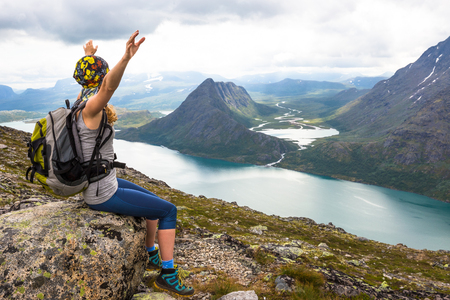 Young woman hiking on Besseggen. Happy girl enjoy lake and good weather in Norway.
