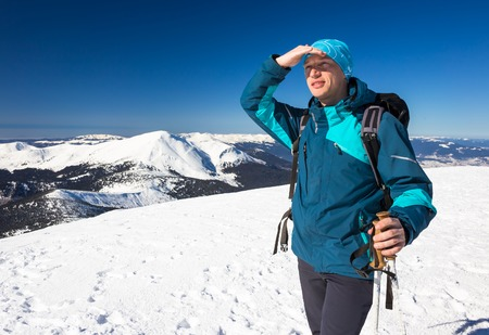 Young happy traveler hiking in beautiful mountains. Fantastic winter landscape. Stock Photo