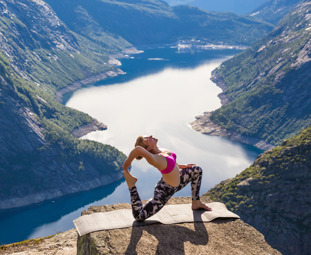 Happy people relax in cliff during trip Norway. Trolltunga hiking route Stock Photo
