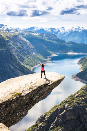 Happy people enjoy an having fun in cliff during trip Norway. Trolltunga hiking route