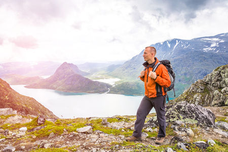Young man hiking on Besseggen. Happy guy enjoy beautiful lake and good weather in Norway. Toning picture