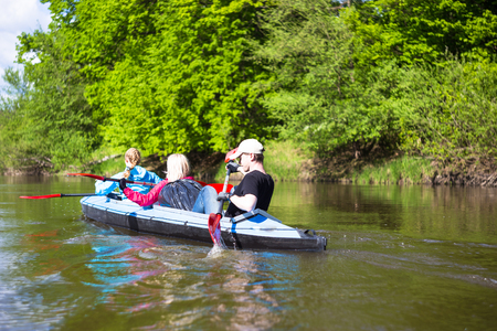 Young people are kayaking on a river in beautiful nature. Summer sunny day