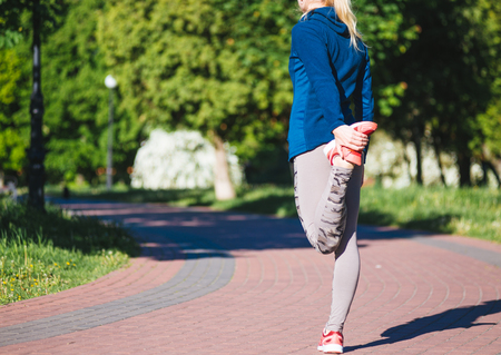 cross legs: Young woman training in city park at summer day, Stock Photo
