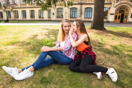 Jóvenes adolescentes felices divirtiéndose en el parque de la ciudad. Buen clima de verano. Novias caminando en el parque.