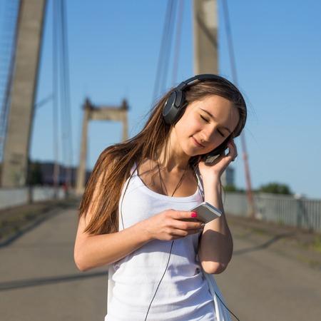 Teenage woman walking in old bridge. Summer hot weather at city