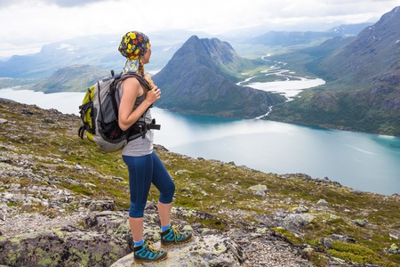 Sport woman hiking on Besseggen. Hikers enjoy beautiful lake and good weather in Norway.