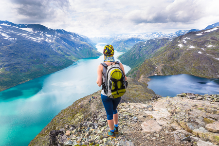 Young woman hiking on Besseggen. Happy girl enjoy beautiful lake and good weather in Norway. Stock Photo